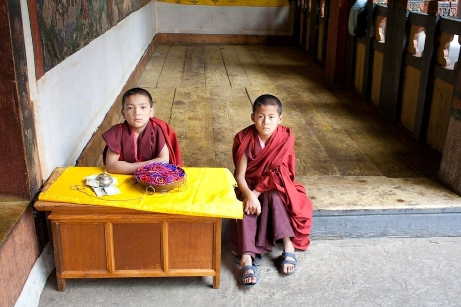 Boy monks at the entrance of a temple in Paro Dzong